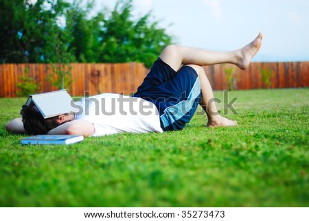 Young man is laying on green ground and learning - stock photo
