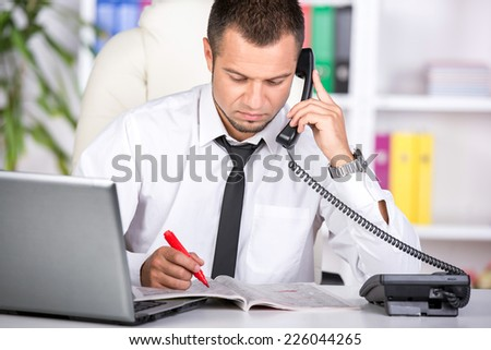 Young man is looking for a job in the newspaper and laptop and calling. - stock photo