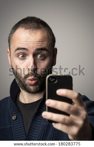 Young man is looking surprised at his phone. - stock photo