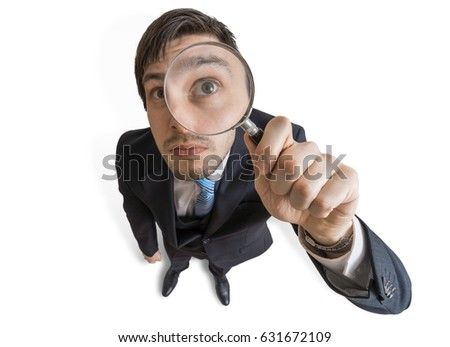 Young man is looking through magnifying glass. Isolated on white background. View from above.