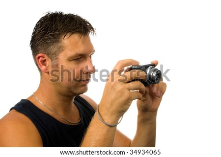 Young man is making a photo with compact camera isolated on white background
