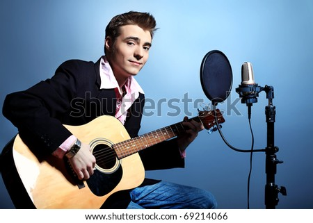 Young man is playing on a guitar at studio, rock'n'roll style. - stock photo