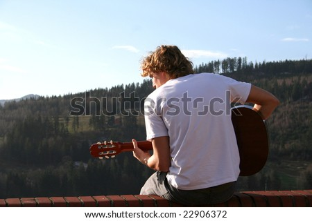 Young man is playing outside, on the roof. Mountain scenery. Mayby he is playing for God and he is worshipping him. He sings. - stock photo