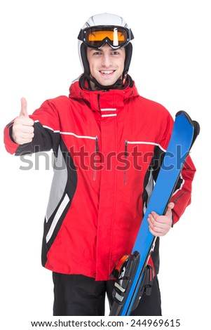 Young man is posing with skis in studio, isolated on white background.