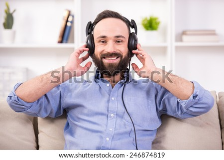 Young man is relaxing at home, listening to music using headphone. - stock photo