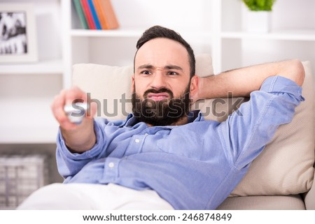 Young man is relaxing at home, using a control remote while watching tv. - stock photo