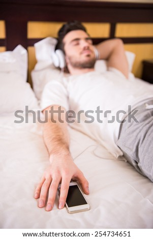 Young man is relaxing while listening to music, lying on bed. - stock photo