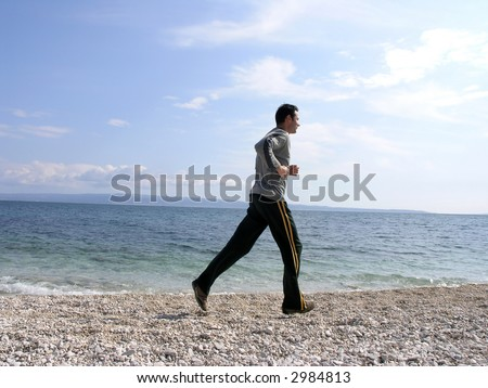 Young man is running along the shore in a sunny day .Space for copy. - stock photo