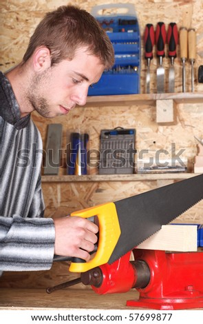 Young man is sawing wood in his lumber