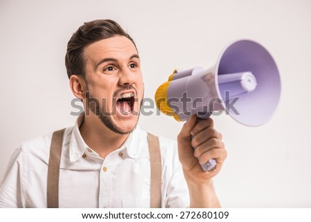 Young man is shouting in a megaphone over grey background. - stock photo