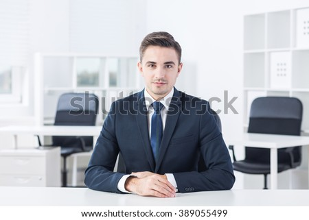 Young man is sitting calmly at his desk