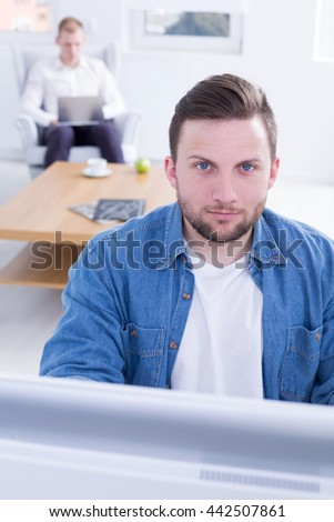 Young man is sitting in front of computer and looking straight with confidence