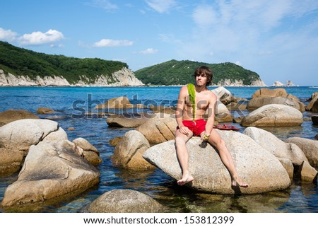 Young man is sitting on a rock by the sea. - stock photo