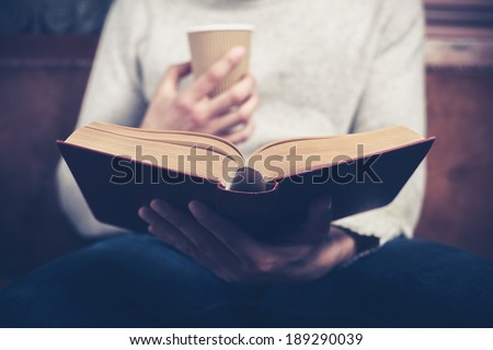Young man is sitting on a sofa and reading a book while holding a paper cup - stock photo