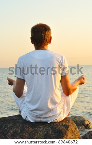 young man is sitting on a stone and looking at sea sunrise. view from behind - stock photo