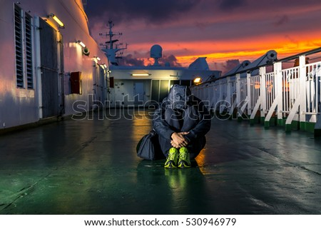 Young man is sitting on the deck during sunset
