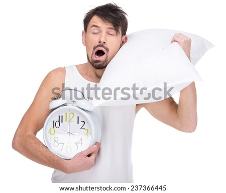 Young man is sleeping with head resting on pillow with clock on the white background. - stock photo