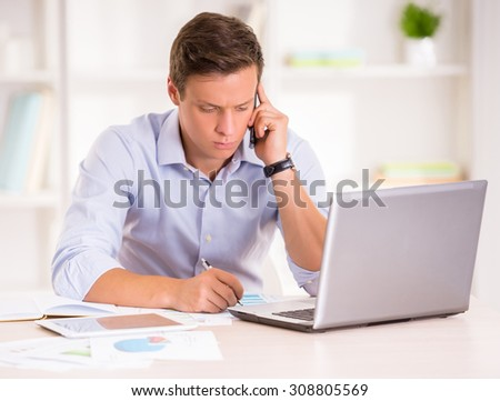 Young man is speaking by phone while working with laptop and documents.