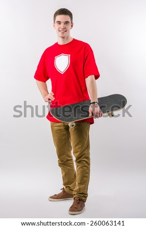 Young man is standing straight, smiling and holding a skateboard in his hand - stock photo
