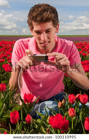Young man is taking pictures in field with tulips in Holland - stock photo