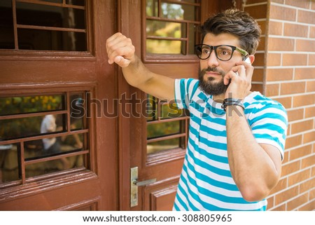 Young man is talking by phone standing near the door. - stock photo
