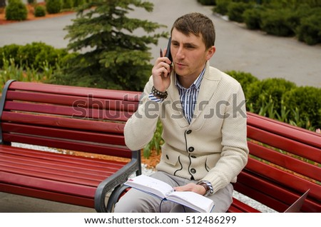 Young man is talking on the phone in park