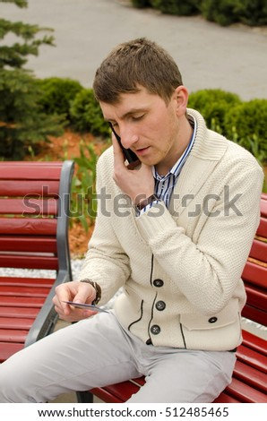 Young man is talking on the phone with card in hand