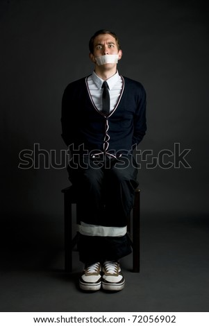 Young man is tied up on a chair. Hostage - stock photo