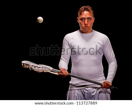 Young man isolated on a black background and wearing white stares at the camera as he catches a lacrosse ball with his stick. - stock photo