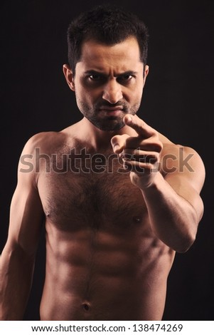Young man isolated on dark background pointing his finger at you - stock photo
