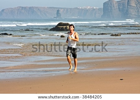 Young man jogging along the beach at the atlantic ocean in Portugal - stock photo
