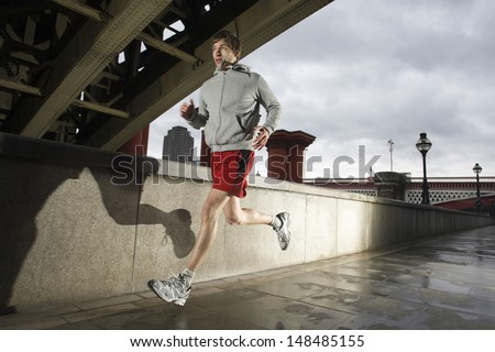 Young man jogging besides the Thames river in London on a stormy day - stock photo