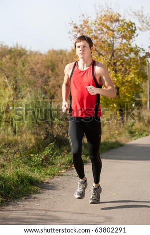 Young man jogging in autumn park