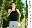 Young man jogging in park. Health and fitness. - stock photo