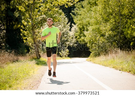 Young man jogging in park on summer sunny day
