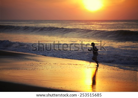 Young man jogging on the wet sand against the sun rising over the ocean - stock photo