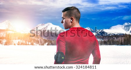 Young man jogging outside in sunny winter mountains - stock photo