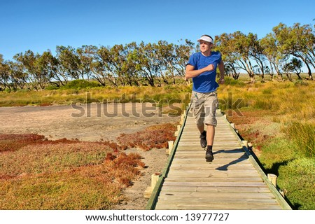 Young man jogs on woodwalk above mangrove marshland. Shot in West Coast Nature Reserve, near Langebaan, Western Cape; South Africa.