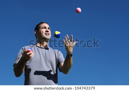 Young man juggler is juggling balls.concept photo of flexibility, success, skill and control.  - stock photo