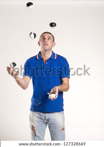 Young man juggling with several balls at once - stock photo