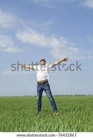young man jumping a green field of grass - stock photo