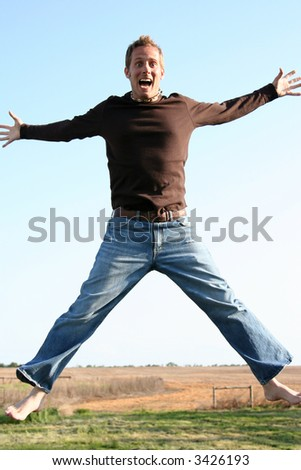 Young man jumping against a blue sky