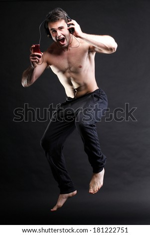 Young man jumping and listening music isolated over a gray background - stock photo