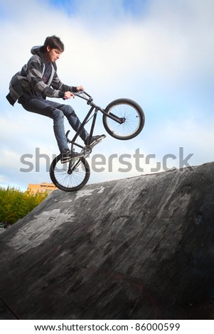 Young man jumping and riding on a BMX bicycle on a ramp over blue sky background