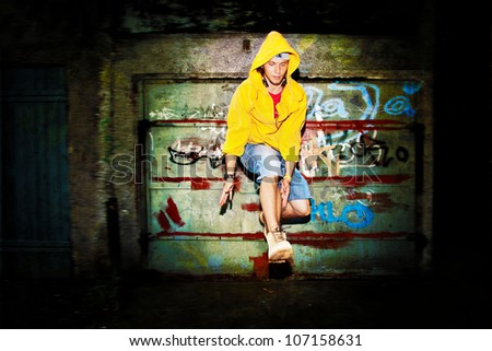 Young man jumping / dancing on grunge graffiti wall background