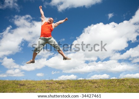 Young man jumping for joy in a beautiful landscape with blue sky and clouds