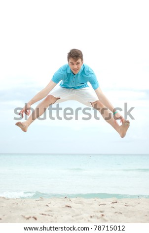 Young man jumping high on the beach - stock photo