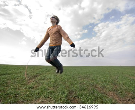 Young man jumping high with a skipping-rope - stock photo