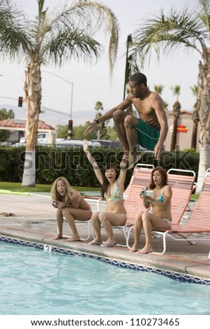 Young man jumping in the pool with friends sitting at pool side - stock photo