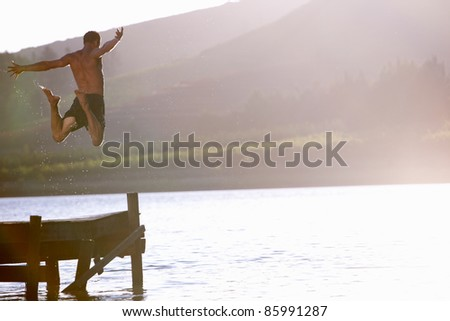 Young man jumping into lake - stock photo